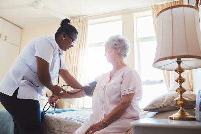 nurse checking blood pressure of elder woman